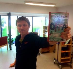Biblioteksjef Einar holder opp en bok med en sort mann på coveret.
